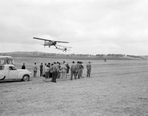 Aerial spraying and crop dusting demonstration on 'Analby' station, the property of Mr J H Dutton, at Kapunda, South Australia. [Crowd watches two planes in the demonstration] [photographic image] / photographer, Cliff Bottomley. 1 photographic negative: b&w, acetate